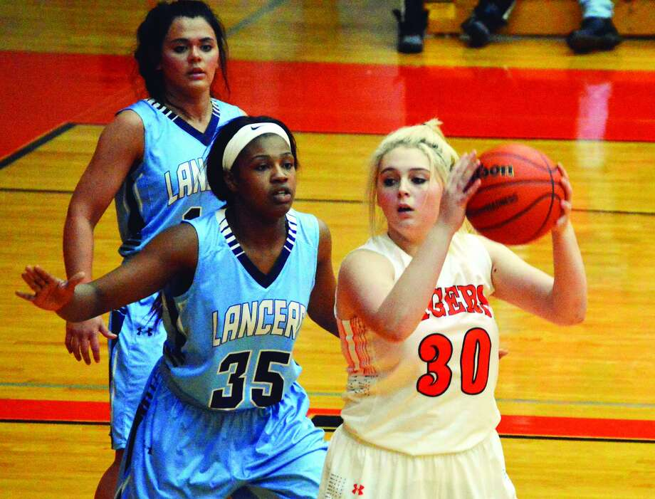 Edwardsville forward Morgan Hulme, right, shields the ball from a defender.