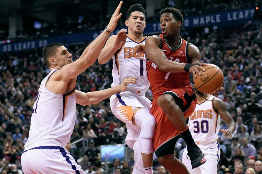 Phoenix Suns' Alex Len (21) and Devin Booker (1) defend as Toronto Raptors guard Kyle Lowry (7) looks to pass the ball during the second half of an NBA basketball game Tuesday, Dec. 5, 2017, in Toronto. (Nathan Denette/The Canadian Press via AP) ORG XMIT: NSD514 Photo: Nathan Denette / The Canadian Press