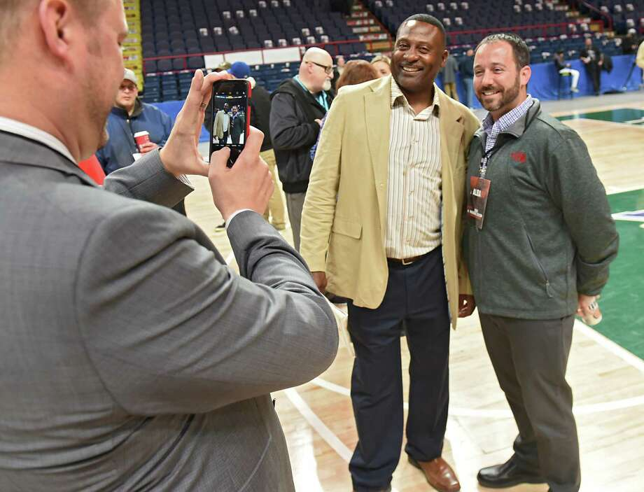 "Former Firebirds football player Eddie Brown (nicknamed ""Touchdown Eddie Brown""), center, has his photo taken with fan Jules Paul of Latham as fans got to meet and greet with the Albany arena football players, coaches and owners during an open house at the Times Union Center on Tuesday, Dec. 5, 2017 in Albany, N.Y. Jules remembered Brown when he coached at Shaker High School. When Jules was younger and living at ValleyView Apartments Brown and the team would throw passes to him and his friends on the front lawn. (Lori Van Buren / Times Union) Photo: Lori Van Buren / 20042314A"
