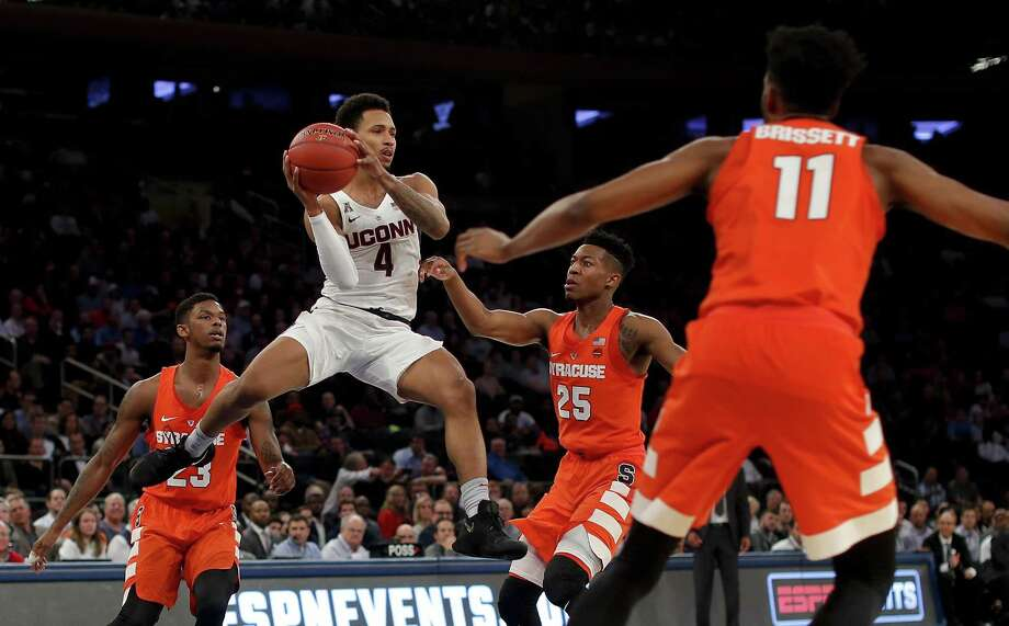 UConn guard Jalen Adams passes the ball off against Syracuse guard Tyus Battle (25), guard Frank Howard (23) and forward Oshae Brissett (11) during the first half on Tuesday. Photo: Julie Jacobson / Associated Press / Copyright 2017 The Associated Press. All rights reserved.