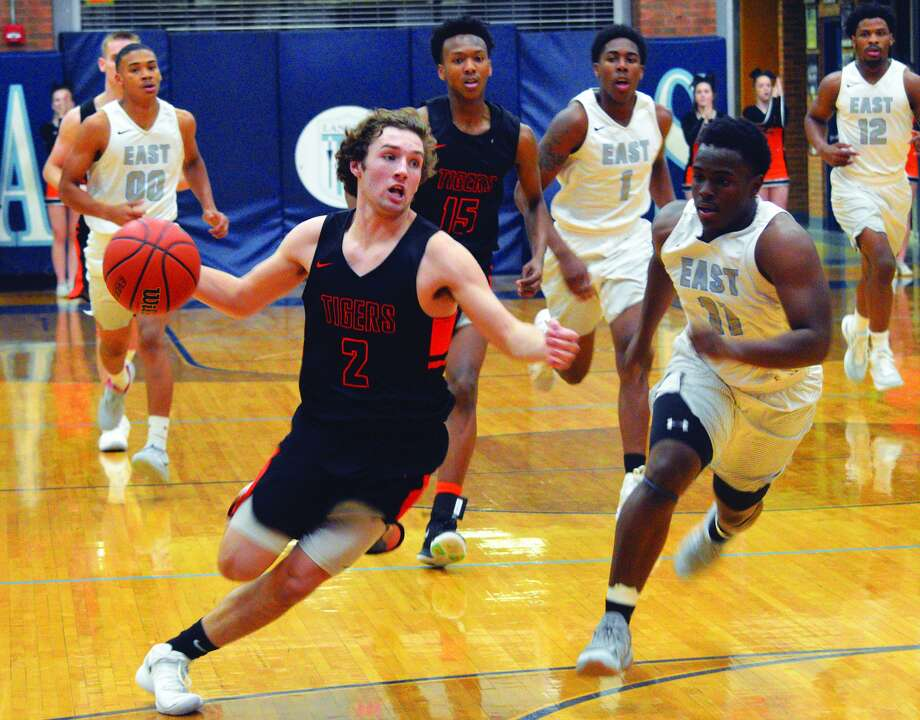 Edwardsville senior Jack Marinko, left, drives to the basket during the second quarter of Tuesday's Southwestern Conference game at Belleville East.