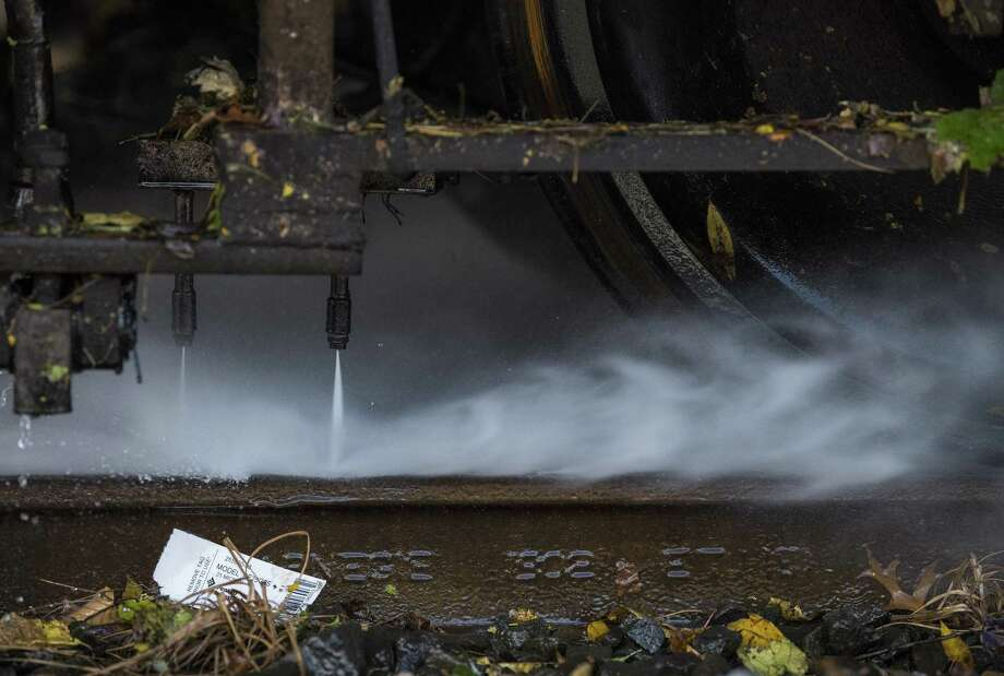 A rail washing train's water jets blast the top of the rail at the Metro-North White Plain Maintenance of Equipment Repair Facility in White Plains, N.Y., Oct. 30, 2017. Every fall a gelatinous goo forms on the rails across the Northeast as leaves are crushed by the wheels of trains, creating a slippery leaf slime that slows them, or even worse, causes them to skid. (Joshua Bright/The New York Times) Photo: JOSHUA BRIGHT / NYT / NYTNS