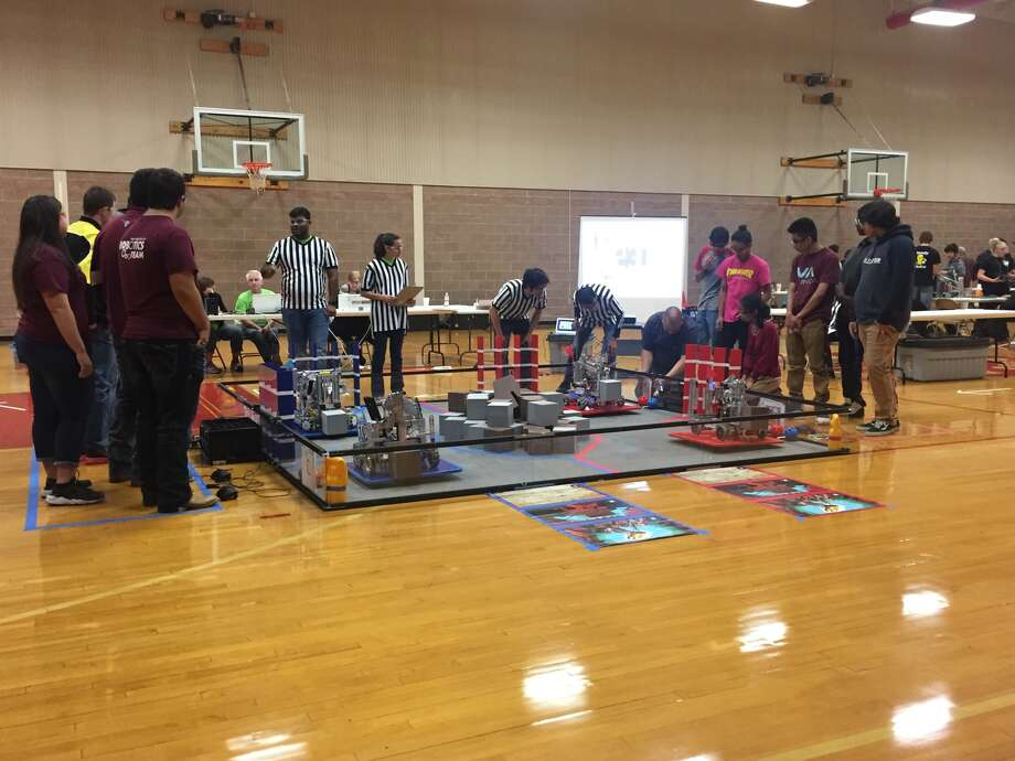 Students prepare their robots during a recent First Tech Challenge competition held at PHS Saturday as the competition's referees look on. Photo: Courtesy Photo