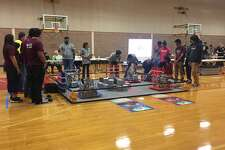 Students prepare their robots during a recent First Tech Challenge competition held at PHS Saturday as the competition's referees look on.