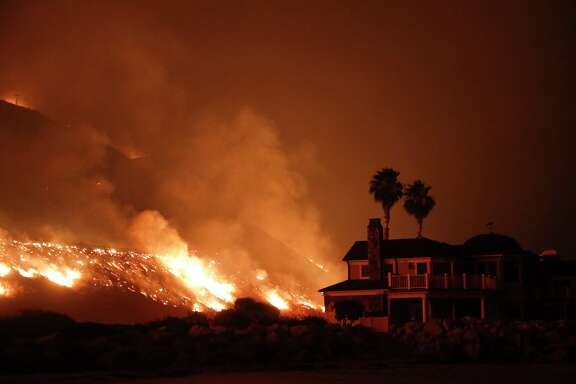 A wildfire threatens homes as it burns along the 101 Freeway Tuesday, Dec. 5, 2017, in Ventura, Calif. Raked by ferocious Santa Ana winds, explosive wildfires northwest of Los Angeles and in the city's foothills burned a psychiatric hospital and scores of homes and other structures Tuesday and forced the evacuation of tens of thousands of people.