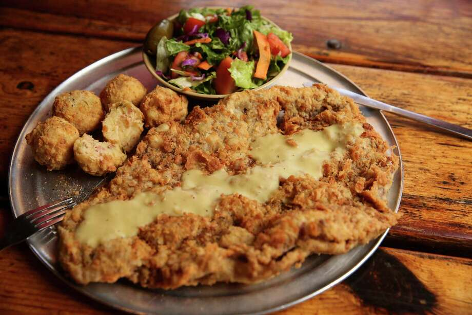 The Rancher Chicken Fried Steak from Hickory Hollow's original Fallbrook location has the largest size of chicken fried steak, side salad and hot tots, which are deep fried mashed potato balls, on Friday, Dec. 1, 2017, in Houston. ( Yi-Chin Lee / Houston Chronicle ) Photo: Yi-Chin Lee, Houston Chronicle / © 2017  Houston Chronicle