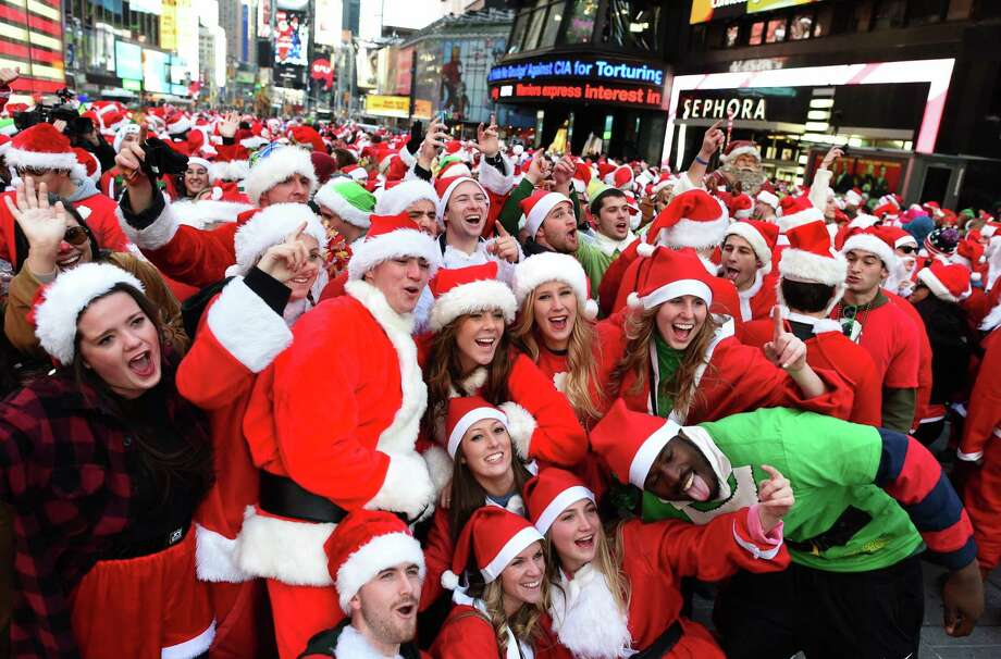 People dressed as Santa Claus and Mrs. Claus pose in Times Square as they gather for the annual Santacon festivities on December 13, 2014 in New York. AFP PHOTO/DON EMMERT        (Photo credit should read DON EMMERT/AFP/Getty Images) Photo: DON EMMERT / AFP/Getty Images / Getty Images
