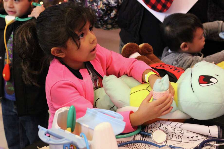 A child gives some attention to her stuffed animal during the Health Museum's Teddy Bear Checkup. Photo: Health Museum