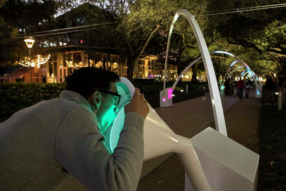 """Luie Duarte speaks into the """"Hello Trees"""" art installation, by  Montreal-based design studio Daily tous les jours, at Discovery Green on Friday, Nov. 24, 2017, in Houston. """"Hello Trees"""" spans the Brown Promenade at Discovery Green, the tree-lined walkway next to the Grove Restaurant. It transforms human voices into sound, music and light that changes as people walk through a series of tubular arches. ( Brett Coomer / Houston Chronicle ) Photo: Brett Coomer, Staff / © 2017 Houston Chronicle"""