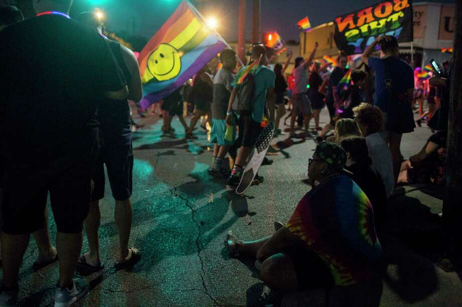 Adam Snow, lower right, watches the parade during Pride in San Antonio. Adam first learned about the LGBTQ peer support group Fiesta Youth at Pride in 2016. Photo: Carolyn Van Houten, San Antonio Express-News / 2017 San Antonio Express-News