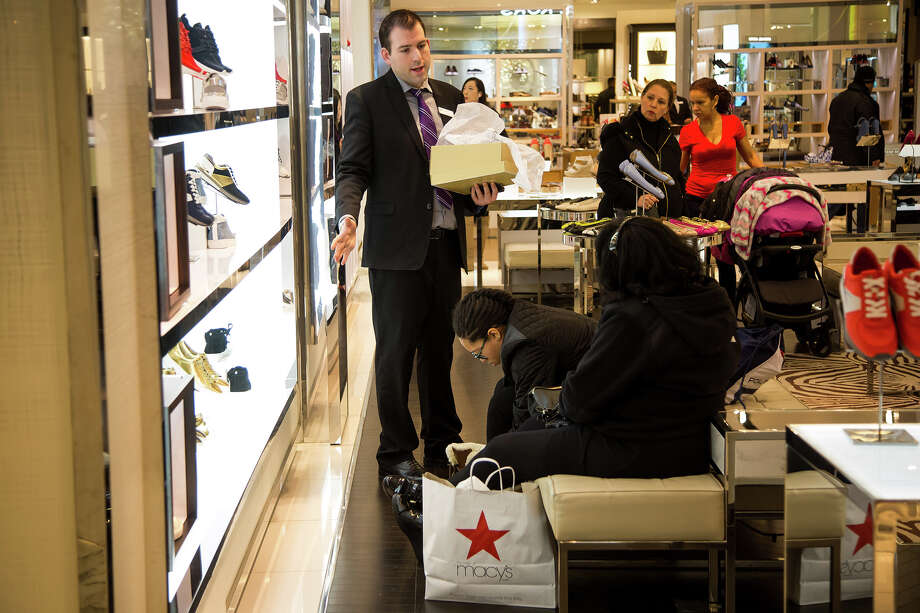 A Macy's employee at left helps customers at a department store in New York on Feb. 22, 2016. ( Photo: Michael Nagle/Bloomberg) / Bloomberg