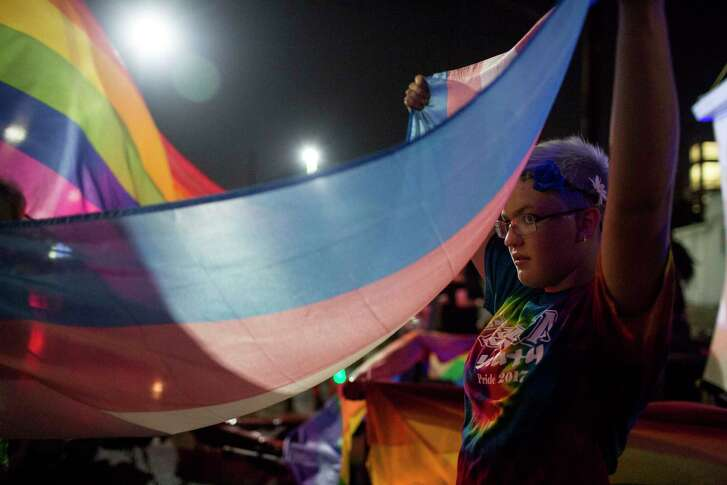 Jaime Merkert carries a trans flag during the Pride Parade in San Antonio.