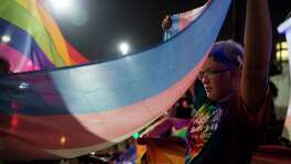 Jaime Merkert carries a trans flag during the Pride Parade in San Antonio.