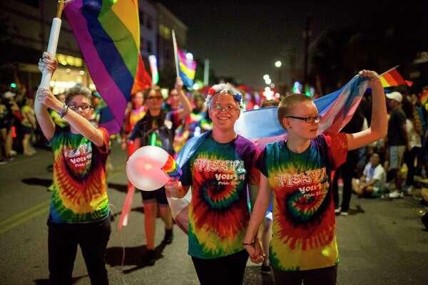 Jaime Merkert, center, carries a trans flag and walks with his friends from Fiesta Youth in San Antonio's Pride Parade.