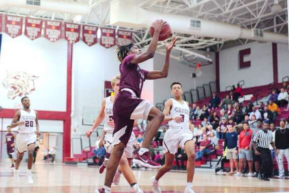 Pearland's Robert Charles sails in for a layup Tuesday night as Clear Creek's defense pursues in a non-district basketball game.