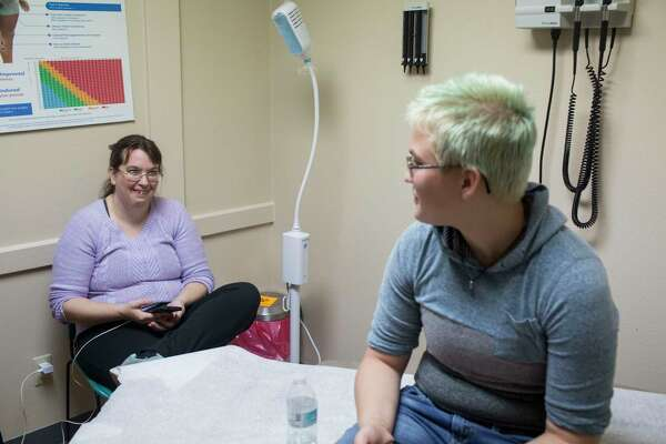 Jaime Merkert talks with his mom Charity Coddington in an exam room while waiting to get a testosterone shot at the Karnes Community Health Center.
