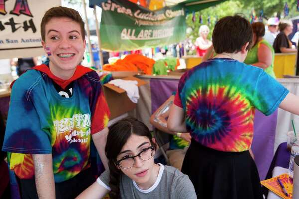 Jackson Farner and Treci Vale hang out at the booth for Fiesta Youth, a LGBTQ peer support group, during San Antonio's Pride celebration.