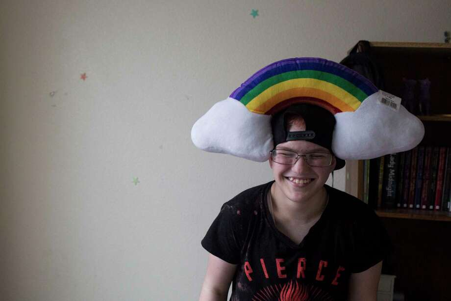 Jaime Merkert laughs after putting a rainbow pillow on his head. He keeps several items denoting transgender pride in his room. Photo: Carolyn Van Houten, San Antonio Express-News / 2017 San Antonio Express-News