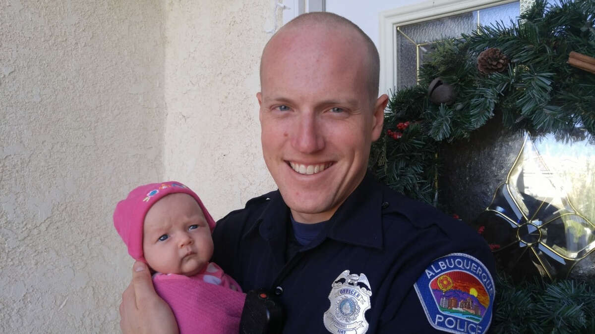Albuquerque Police Officer Ryan Holets with his newborn baby, Hope. In his six years on the force, he has been shot at twice and experienced several near-death encounters. Officer Holets and his wife adopted a baby from parents who suffered from opioid addiction, breaking down walls between drug addicts and police officers to help save lives.