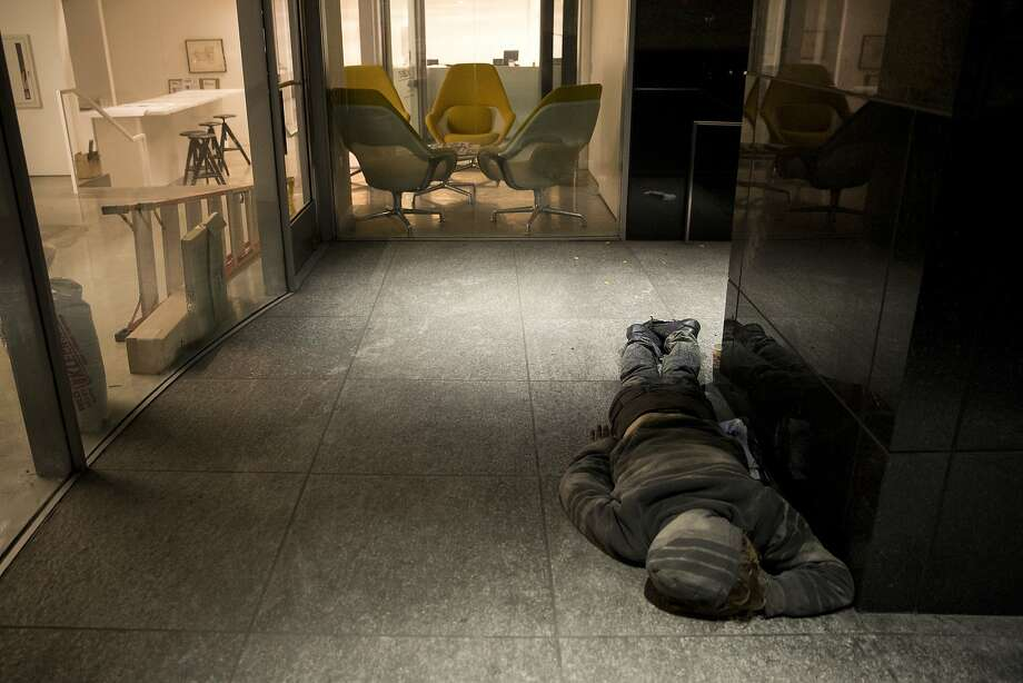 A homeless man sleeps on a concrete floor outside an office building under renovation in Los Angeles. Photo: Jae C. Hong, Associated Press
