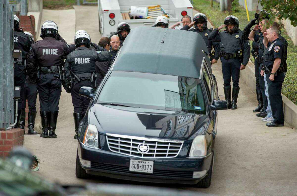 San Marcos Police Chief Chase Stapp, far right, salutes with other officers, as the body of San Marcos Police officer Kenneth Copeland is transferred to a hearse at the Travis County Medical Examiner's Office in Austin, Texas, on Tuesday Dec. 5, 2017. Copeland was killed Monday while he was serving a warrant on a suspect, according to a police statement.(Jay Janner/Austin American-Statesman via AP)
