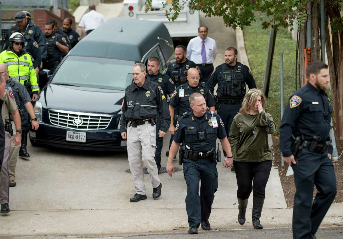 San Marcos Police Chief Chase Stapp, front, walks away after the body of San Marcos Police officer Kenneth Copeland was transferred to a hearse at the Travis County Medical Examiner's Office in Austin, Texas, on Tuesday Dec. 5, 2017. Copeland was killed Monday while he was serving a warrant on a suspect, according to a police statement.(Jay Janner/Austin American-Statesman via AP)