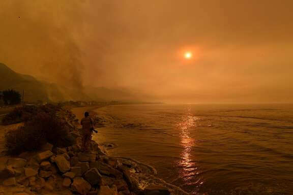 Heavy smoke covers the seaside enclave of Mondos Beach beside the 101 highway as flames reach the coast during the Thomas wildfire near Ventura, California on December 6, 2017. California motorists commuted past a blazing inferno Wednesday as wind-whipped wildfires raged across the Los Angeles region, with flames  triggering the closure of a major freeway and mandatory evacuations in an area dotted with mansions. / AFP PHOTO / MARK RALSTONMARK RALSTON/AFP/Getty Images