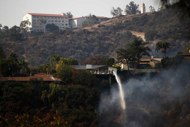 A firefighter puts out a spot fire burning along a hillside, Wednesday, Dec. 6, 2017, in the Bel-Air neighborhood of Los Angeles. A dangerous new wildfire erupted in the tony Bel Air area of Los Angeles early Wednesday as firefighters battled three other destructive blazes across Southern California.