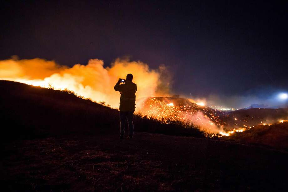 A man watches as the Creek Fire burns along a hillside near homes in the Shadow Hills neighborhood of Los Angeles, California, on December 5, 2017. More than a thousand firefighters were struggling to contain a wind-whipped brush fire in southern California on December 5 that has left at least one person dead, sent thousands fleeing, and was choking the area with thick black smoke. Photo: KYLE GRILLOT, AFP/Getty Images