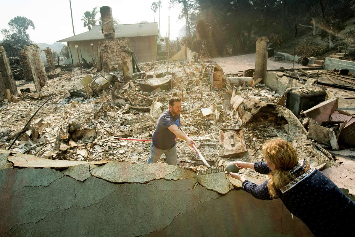 Paul Mattesich hands a jar to his wife Erica Mattesich while sifting through rubble at his family's Ventura, Calif., home following the Thomas fire on Wednesday, Dec. 6, 2017.