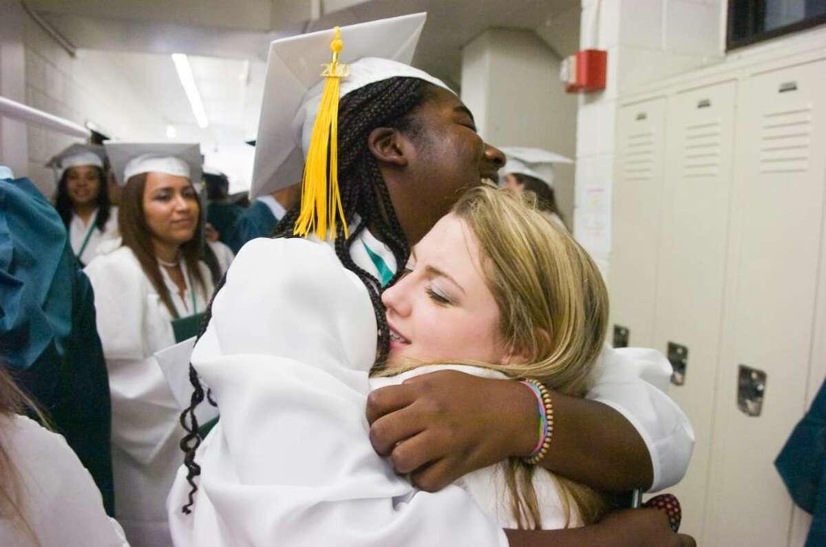 Nicole Monahan gets a hug from fellow graduate Eamari Bell after the Norwalk High School Class of 2010 graduation Monday, June 28, 2010