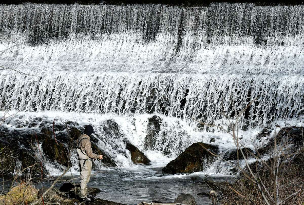 A cold-weather angler drops his line into the tepid waters below Burden Pond on Wednesday, Dec. 6, 2017, in Troy, N.Y. (Will Waldron/Times Union)