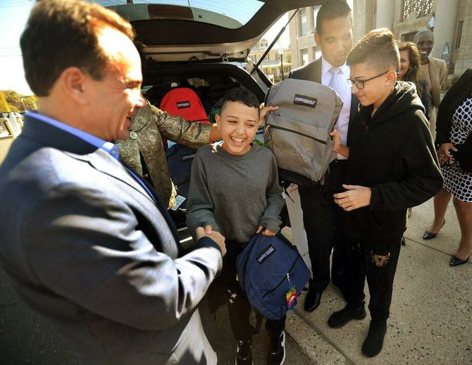 From left; Bridgeport Mayor Joe Ganim gives school backpacks to brothers Juan, 12, and Jan Casiano, 13, from Bayamon, Puerto Rico, outside City Hall in Bridgeport, Conn. on Thursday, October 5, 2017. The brothers, who are staying with Bridgeport relatives following the devastating hurricane in Puerto Rico, will begin attending Luis Munoz Marin School next week. Photo: Brian A. Pounds / Hearst Connecticut Media / Connecticut Post