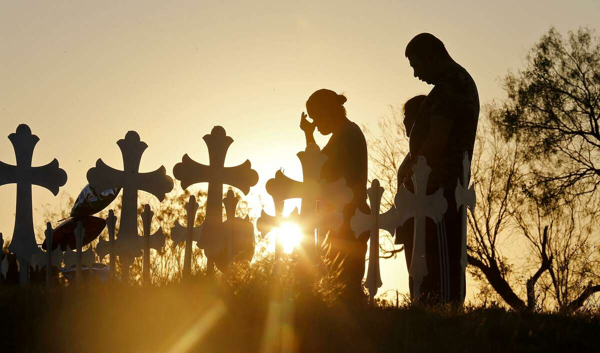 Irene (left) and Kenneth Hernandez (right) with their daughter Miranda pray at the 26 crosses for those killed in the mass shooting at First Baptist Church of Sutherland Springs in November.