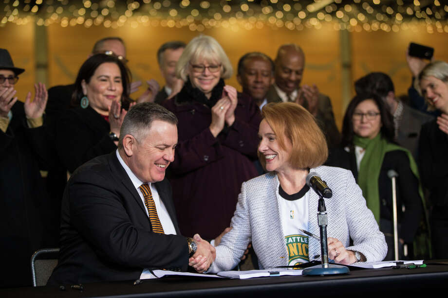 Mayor Jenny Durkan and Chief executive officer of Oak View Group, Tim Leiweke, shake hands after signing an MOU in regards to the KeyArena renovation, at Fisher Pavilion on Wednesday, Dec. 6, 2017. Photo: GRANT HINDSLEY, SEATTLEPI.COM / SEATTLEPI.COM