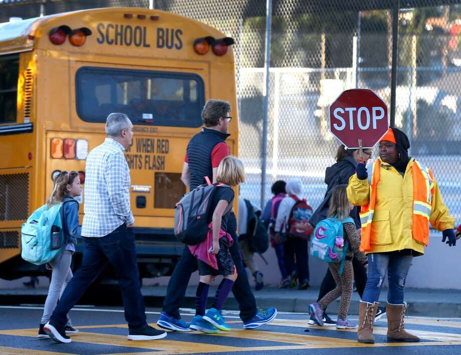 In this file photo, Oakland students walk across a street to board a bus.