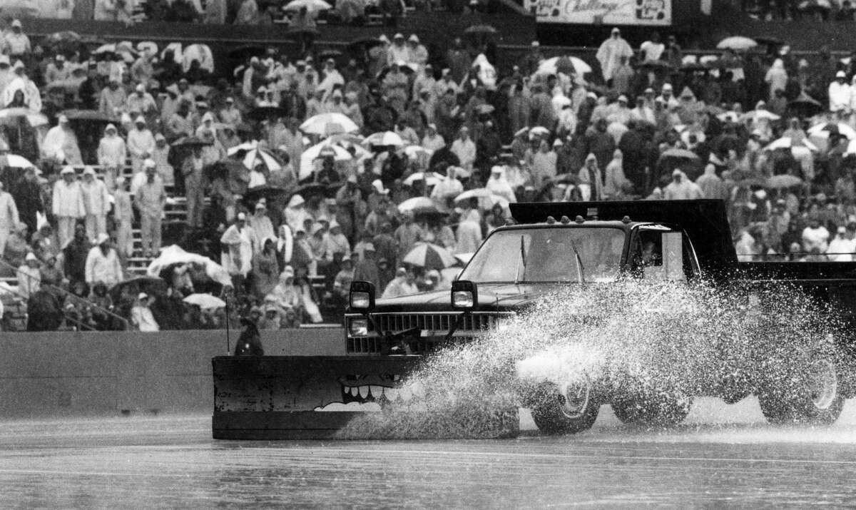 A truck equipped with a squeegee snowplow blade removes the excess water from the playing surface during half time of the season opener between the New England Patriots and Miami Dolphins game at Sullivan Stadium in Foxborough, Mass., on Sept. 13, 1987. (Photo by Paul R. Benoit/The Boston Globe via Getty Images)