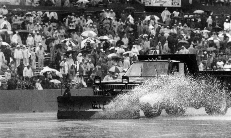 A truck equipped with a squeegee snowplow blade removes the excess water from the playing surface during half time of the season opener between the New England Patriots and Miami Dolphins game at Sullivan Stadium in Foxborough, Mass., on Sept. 13, 1987.  (Photo by Paul R. Benoit/The Boston Globe via Getty Images) Photo: Boston Globe/Boston Globe Via Getty Images