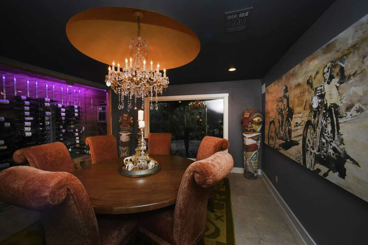 """The dining room of the Montoya/Walsdorf house features a circular table under a crystal chandelier in a recessed dome. The wine cellar, which takes up an entire wall, emits violet light. One of the favorite works of art in the house is the painting by Holly Hein and Bryson Brooks, inspired by the motorcycle film """"Easy Rider."""""""