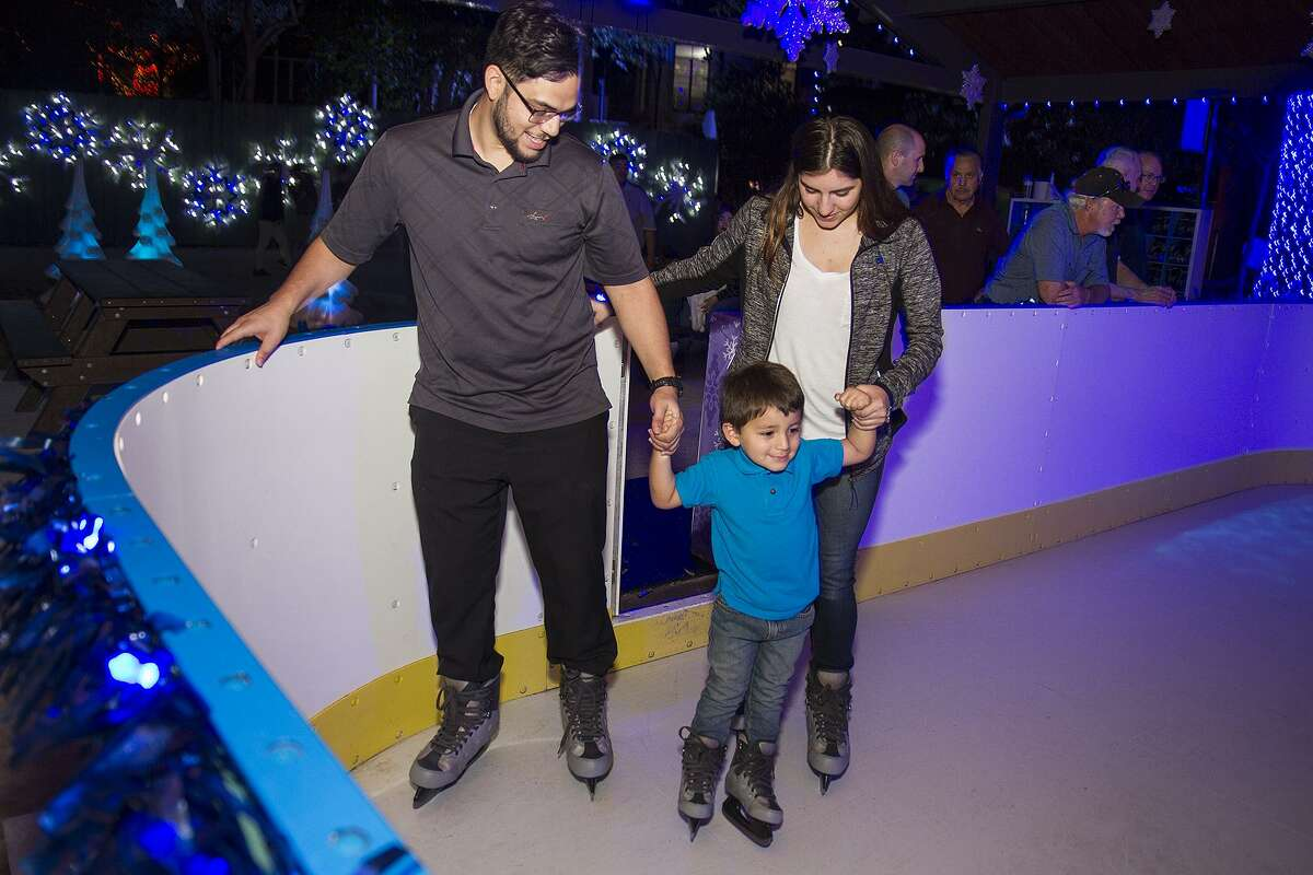 Anthony Garza, 3, ice skates with his parents Adam Garza and Starr Moreno at the zoo during the Zoo Lights holiday celebration, Monday, Dec. 4, 2017.