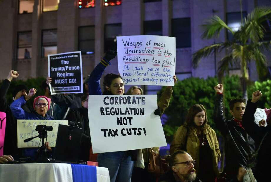 "Demonstrators in Los Angeles protest the ""tax reform"" bills recently passed by the Senate on Dec. 4. The Senate version and the one passed by the House of Representatives earlier must now be reconciled into a single bill, and approved again by both chambers, before it can be signed into law. Both versions dramatically lower the corporate tax rate from 35 percent to 20 percent, and include more modest tax cuts aimed at individuals across all income levels. Photo: FREDERIC J. BROWN /AFP /Getty Images / AFP or licensors"