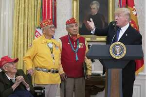 """President Donald Trump, in front of a portrait of Andrew Jackson, delivers remarks alongside Navajo code talkers including Peter MacDonald, center, and Thomas Begay, second from left, during an event at the White House Nov. 27. Trump used the White House event honoring Navajo veterans of World War II to utter one of his favorite Native American-related insult of a political opponent, deriding Sen. Elizabeth Warren (D-Mass.) as """"Pocahontas."""""""