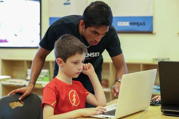 Code Ninjas Sensei Bharath Balabaskar aids Jake Bellard, 9, with codes Tuesday, Nov. 28, 2017, in Pearland. ( Steve Gonzales / Houston Chronicle )