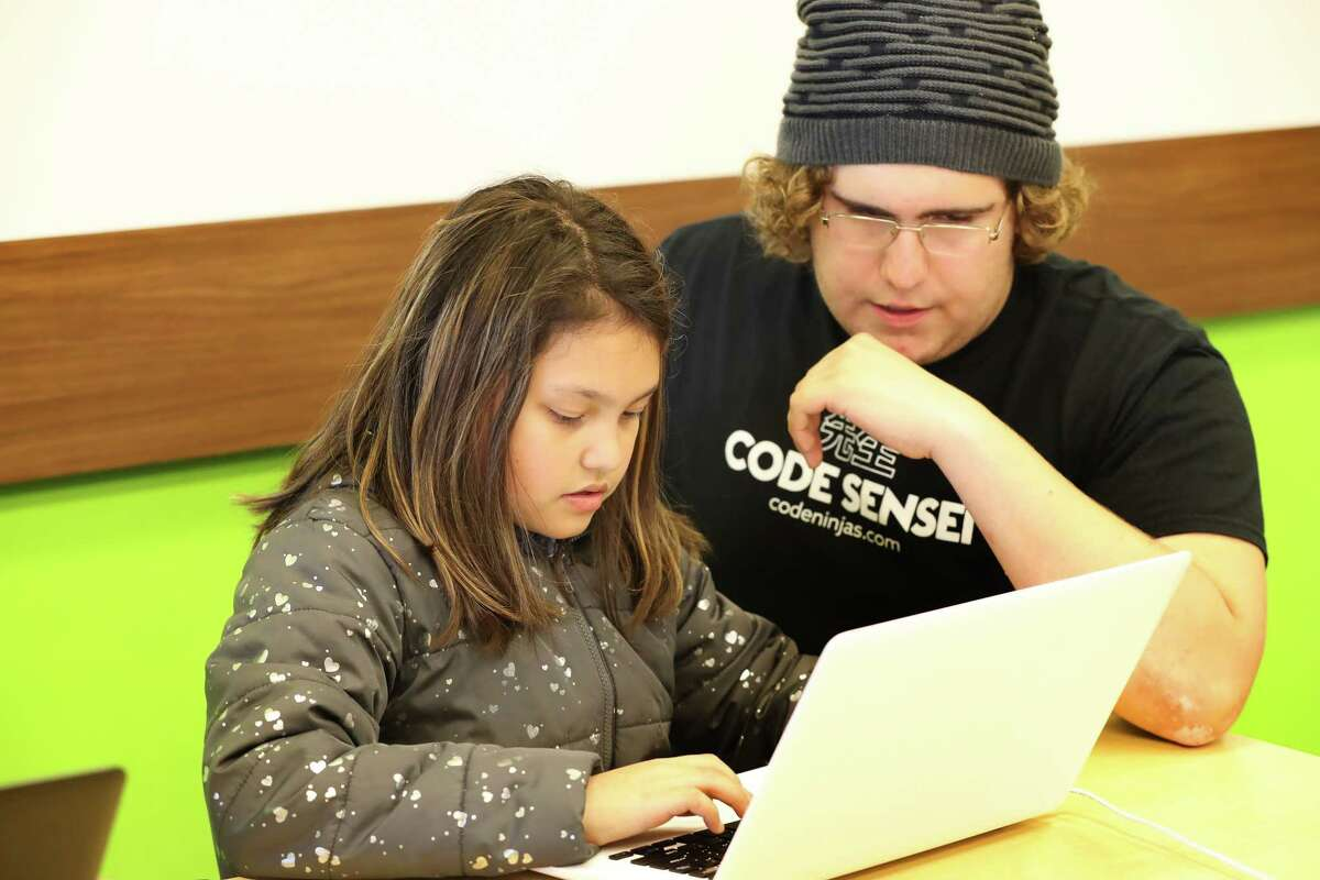 Code Ninjas Sensei Tyler Thames aids Samantha Mullins, 9, with codes Tuesday, Nov. 28, 2017, in Pearland. ( Steve Gonzales / Houston Chronicle )