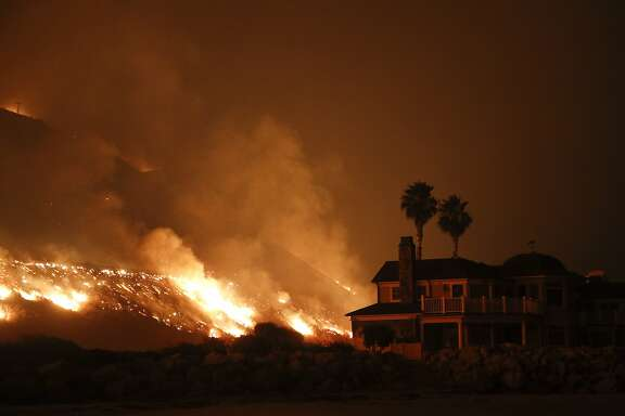 A wildfire threatens homes as it burns along the 101 Freeway Tuesday, Dec. 5, 2017, in Ventura, Calif. Raked by ferocious Santa Ana winds, explosive wildfires northwest of Los Angeles and in the city's foothills burned a psychiatric hospital and scores of homes and other structures Tuesday and forced the evacuation of tens of thousands of people. (AP Photo/Jae C. Hong)