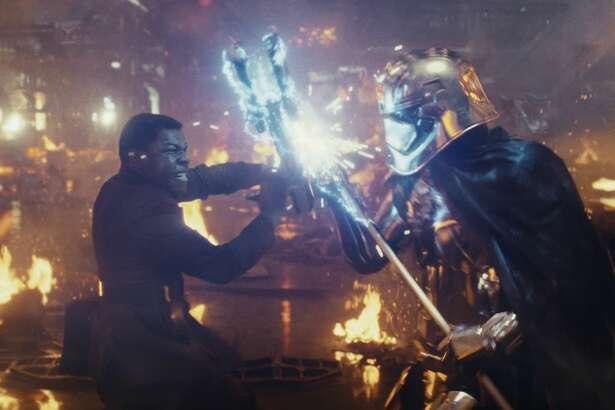 "John Boyega as Finn battling Gwendoline Christie as Captain Phasmain a still image from ""Star Wars: The Last Jedi."""