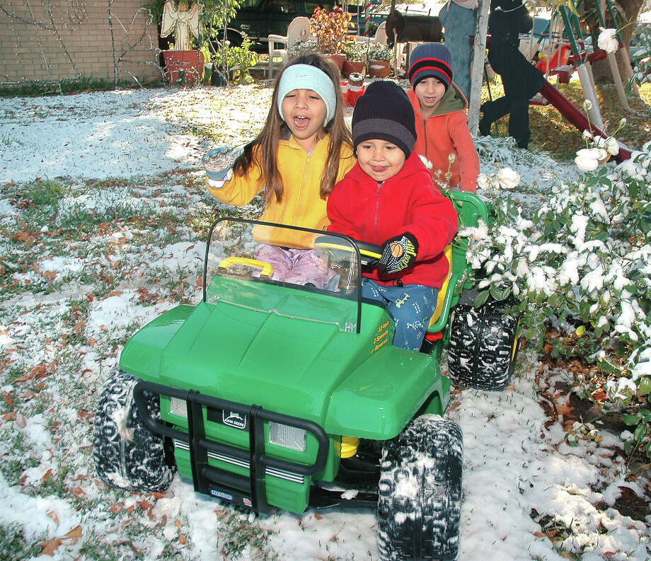"Munoz Family members MaCayla Rey, Patrick James and Phillip play in the snow as they tryout their Christmas present, a ""Gator"" John Deere Tractor in Laredo, Texas,  Saturday, Dec. 25,2004. Laredo, like other cities in South Texas celebrated their first ever White Christmas. Photo: Cuate Santos/Laredo Morning Times"