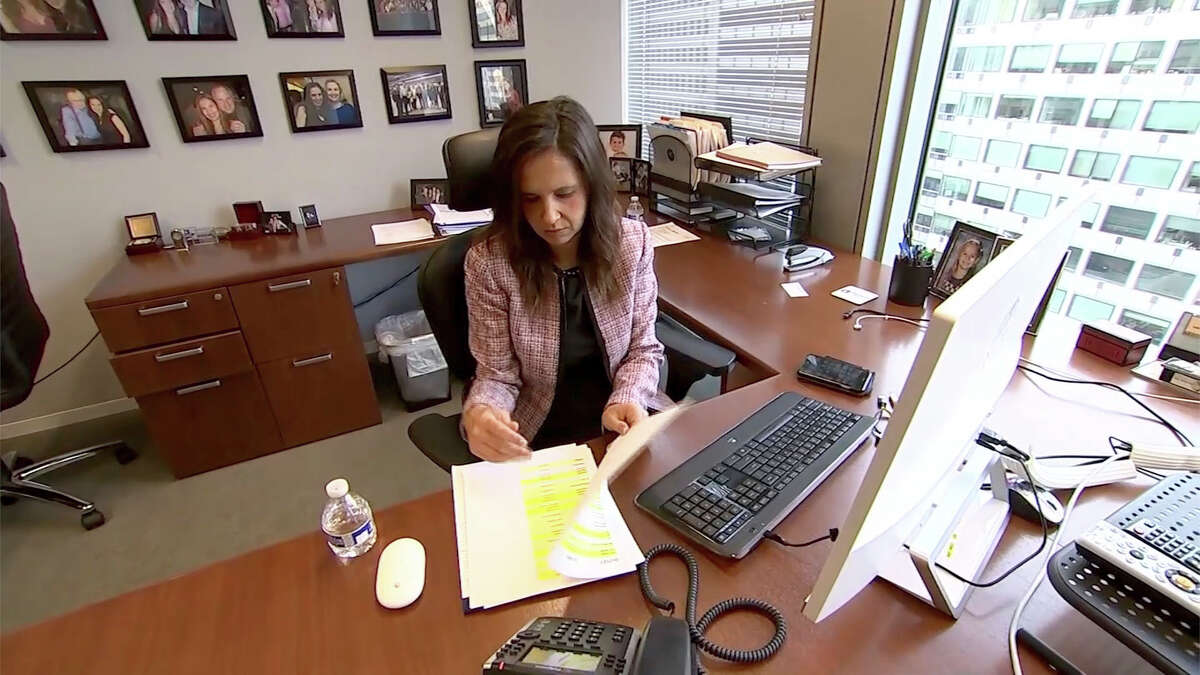 In this Dec. 4, 2017, image made from a video, Eleanor McManus works at her desk at Trident DMG, the Washington public relations firm she co-founded. McManus formed a support group for women like her who say they were victimized by powerful men in the television news business and is the co-founder of Press Forward, an initative aimed at changing newsroom culture. (AP Photo/Dan Huff)