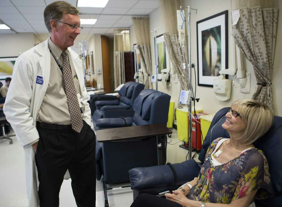 Dr. Kent Osborne, director of Baylor College of Medicine's Dan L. Duncan Cancer Center, visits his patient Carole Roush while she undergoes chemotherapy in 2015. Osborne was here to attend the 40th annual San Antonio Breast Cancer Symposium, which he has co-directed since 1992. ( Marie D. De Jesus / Houston Chronicle ) Photo: Marie D. De Jesus /Houston Chronicle / © 2015 Houston Chronicle