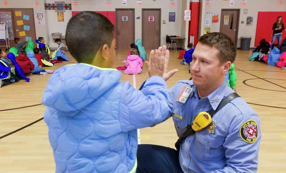Conroe Firefighter Peter Taylor gives a student a high-five as firefighters with theéŠConroe Professional Firefighters AssociationéŠdelivered 136 coats to lower-income students at PattersonéŠElementary SchooléŠas part of their annual winter giving event, Wednesday, Dec. 6, 2017, in Conroe. Photo: Jason Fochtman, Staff Photographer / © 2017 Houston Chronicle